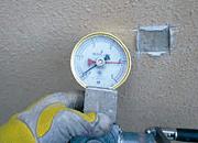 写真:現状塗膜の下地への付着強度を計器で測定